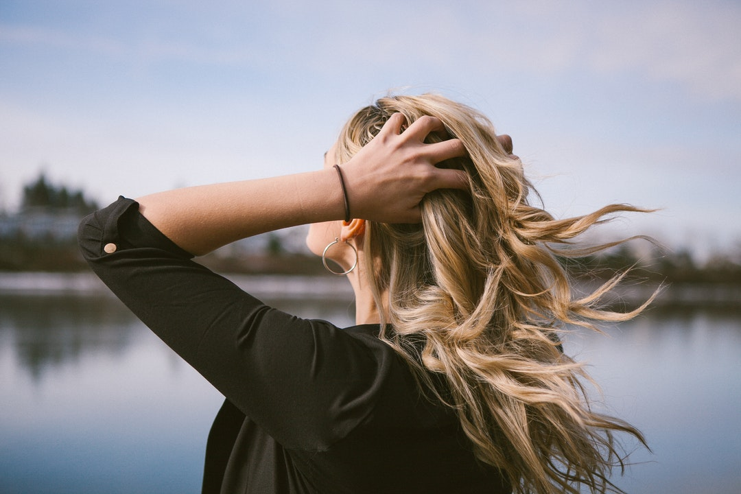 woman holding her blonde hair near body of water at daytime