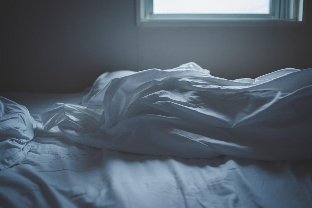 white blanket on bed near window