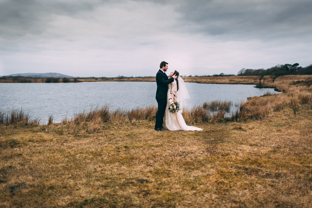 bride and groom photography on brown grass near body of water during daytime