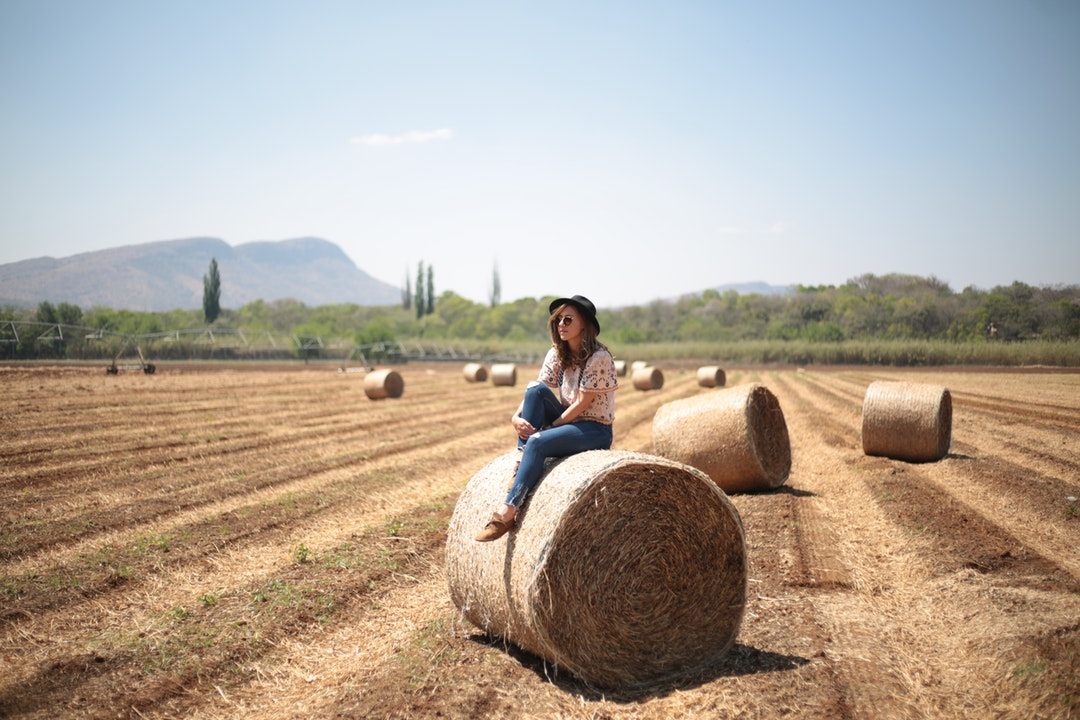 woman sitting on round hale bale