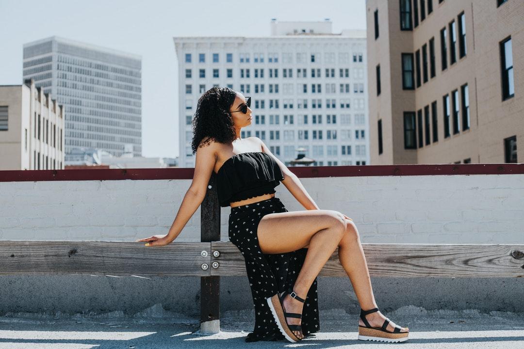 woman sitting near white concrete fence