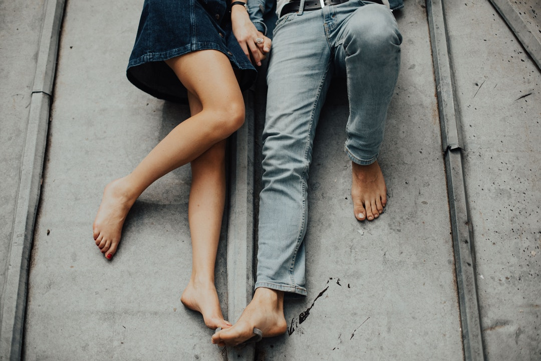 man and woman laying on gray concrete floor