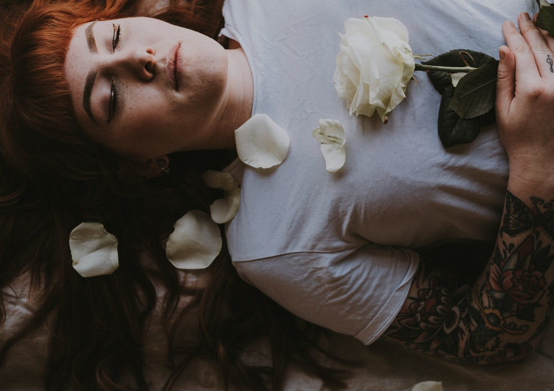 woman sleeping holding white rose flower
