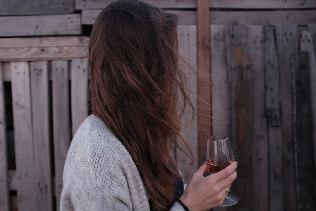 woman holding wine glass standing in front of wooden fence
