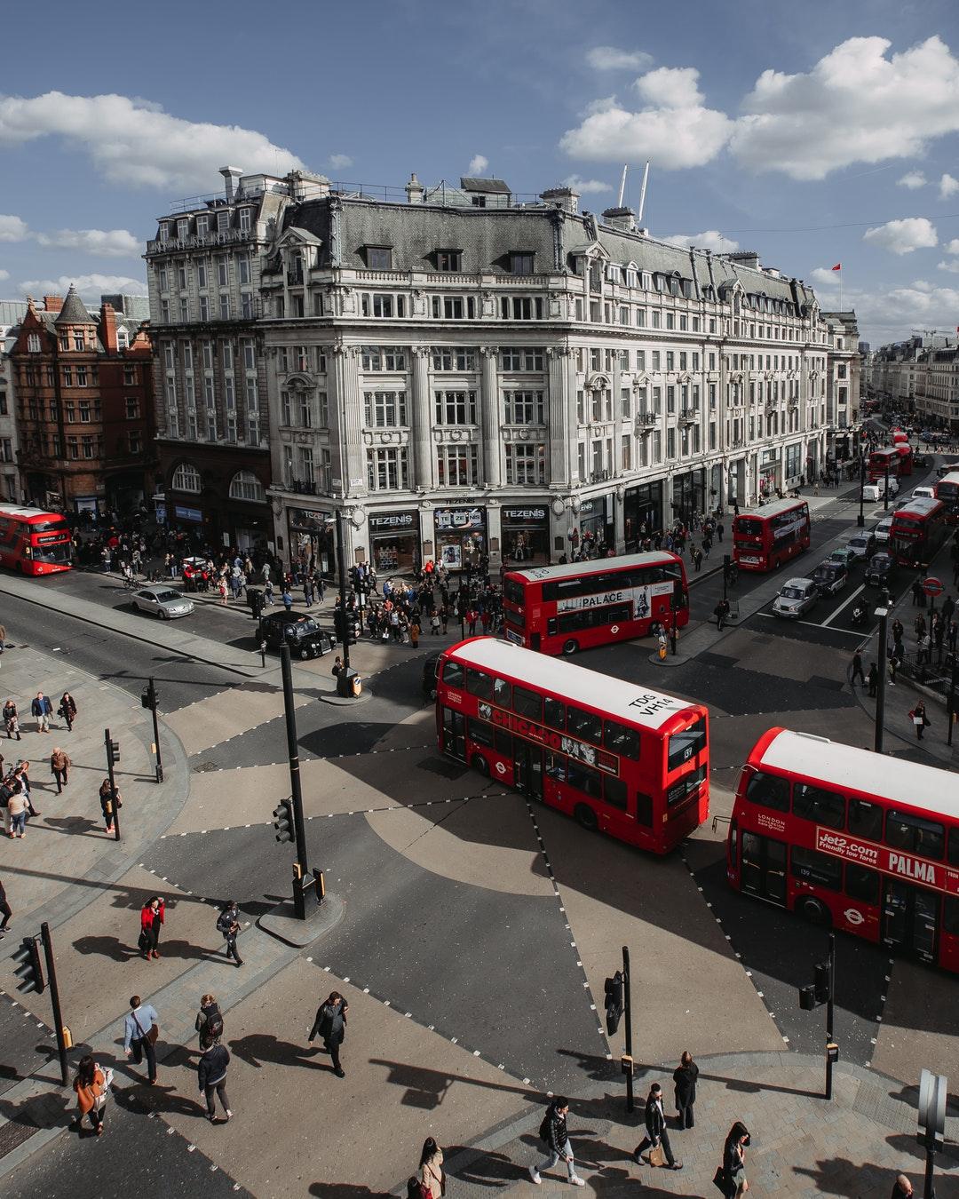 people walking on street near red double-deck buses