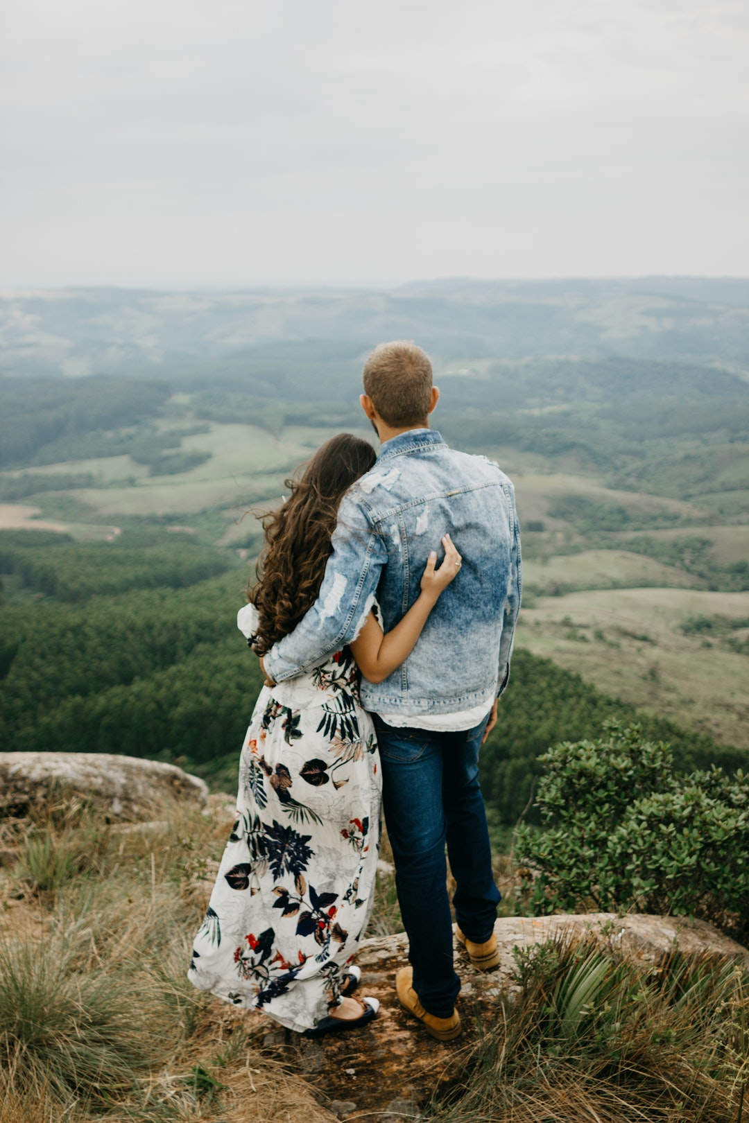 man and woman standing on cliff during daytime