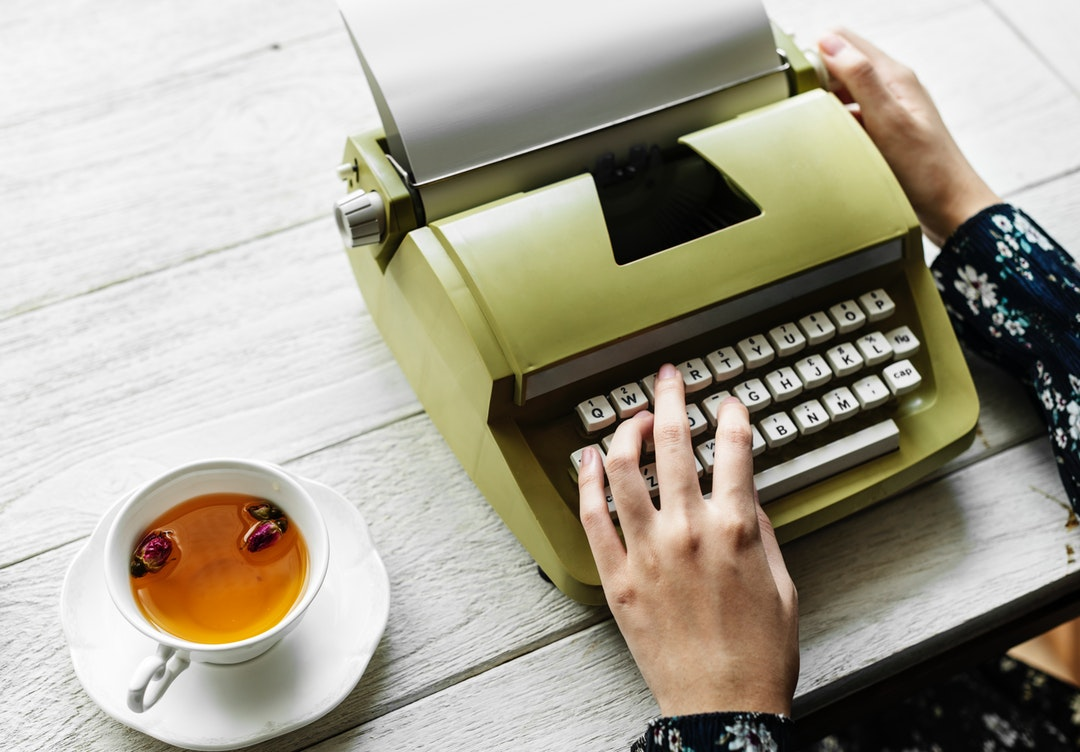flat-lay photography of person using typewriter beside cup of tea