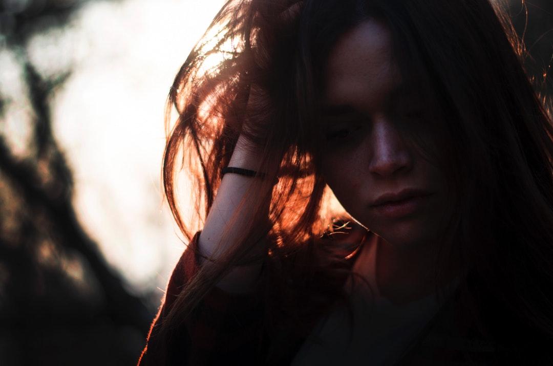 woman left hand on hair under sunset