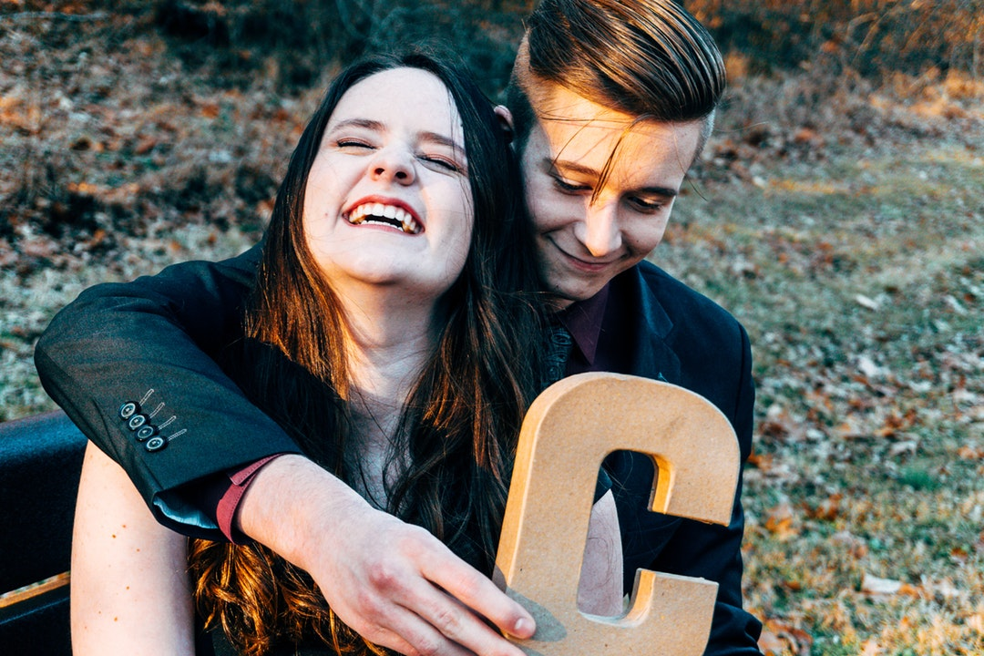 boy hugging girl while holding C letter cutout