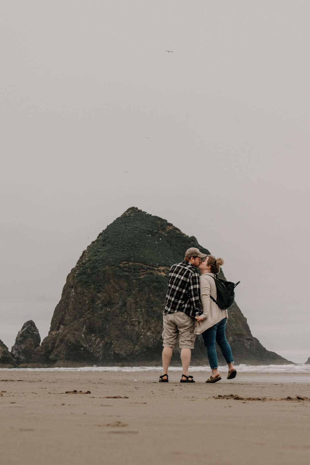 man and woman kissing near islet