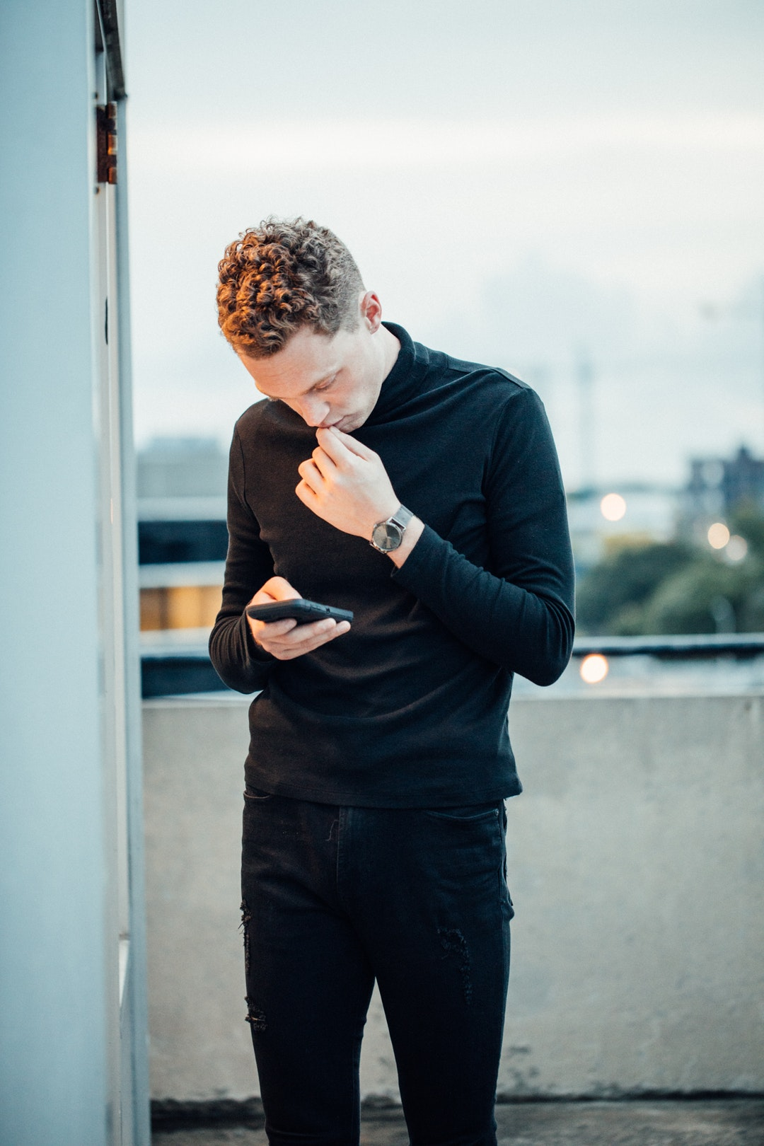 man stand holding smartphone