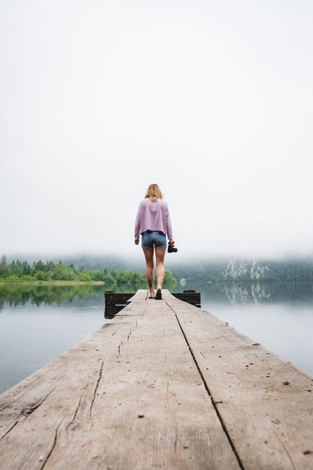 woman walking on dockside beside body of water