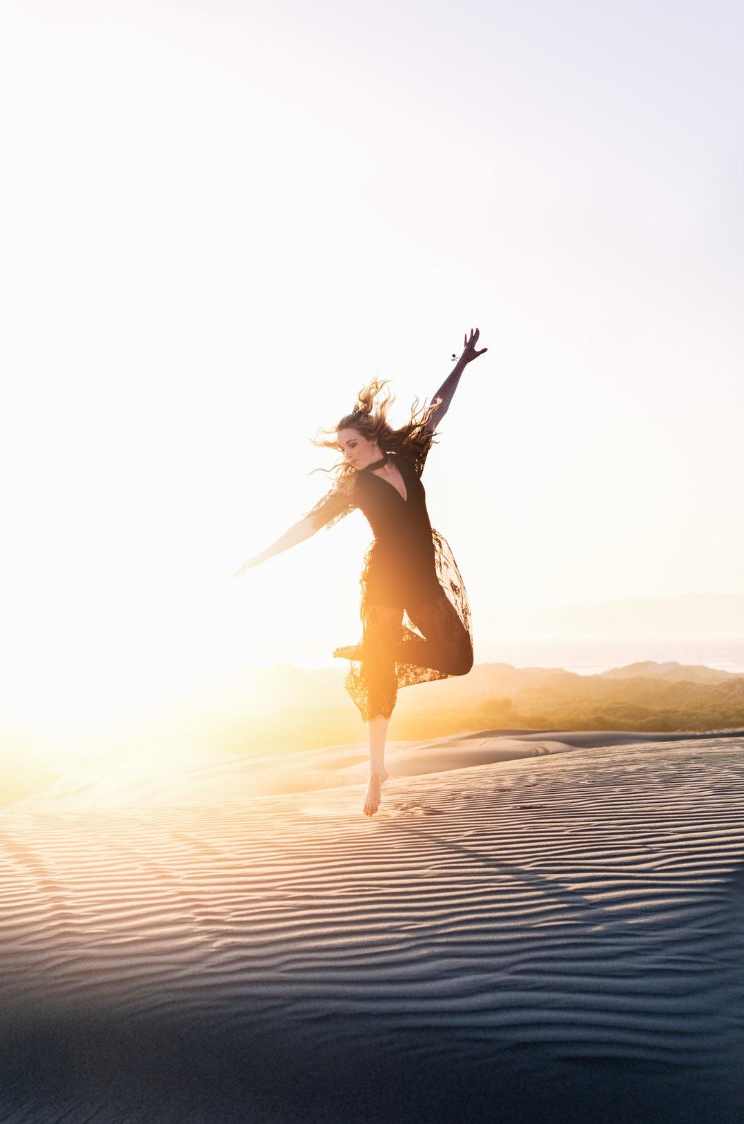 woman walking on desert during sunset