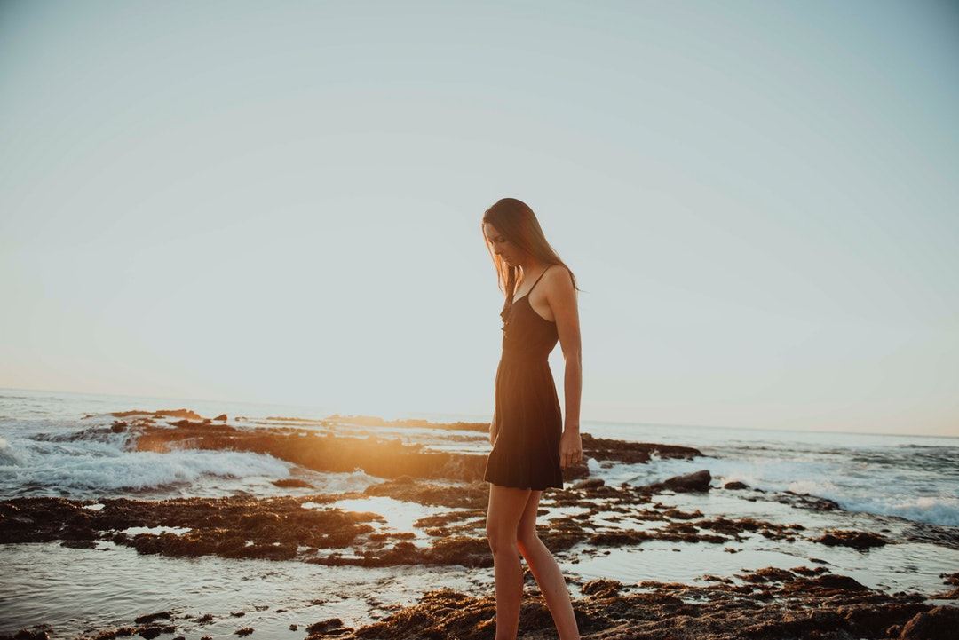 woman in black spaghetti strap dress walking on rock formation surrounded by body of water during daytime