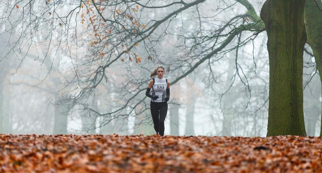 running woman under bare tree during daytime