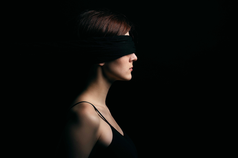 woman wearing black blindfold facing sideways