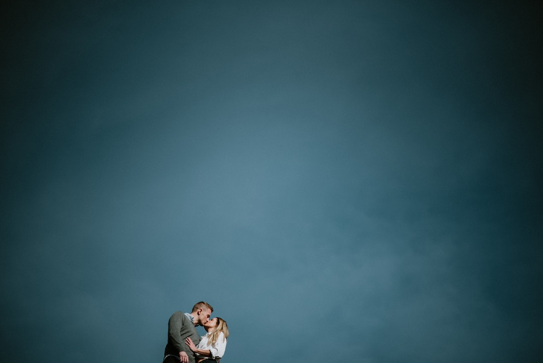 low angle photography of couple kissing under blue sky