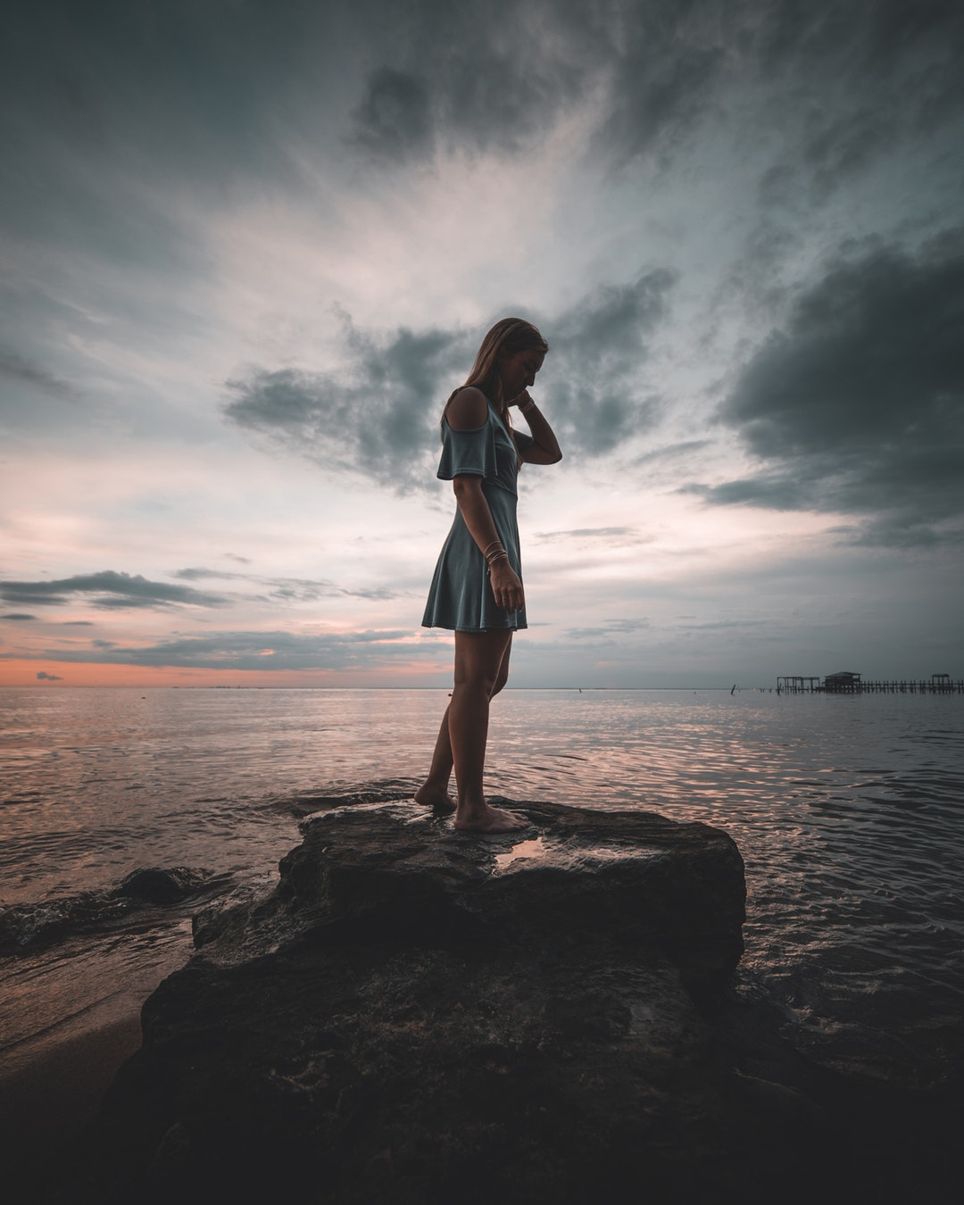 woman standing on rock near body of water