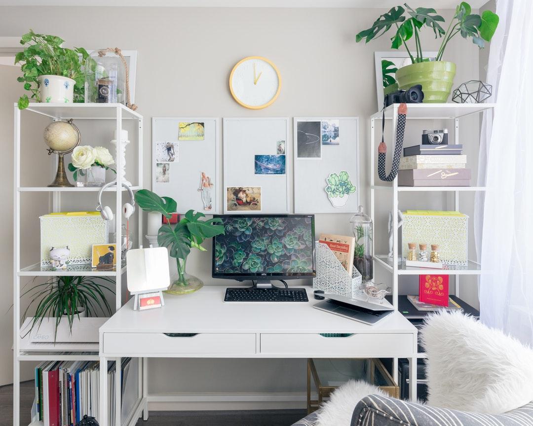 turned on flat screen monitor white wooden desk