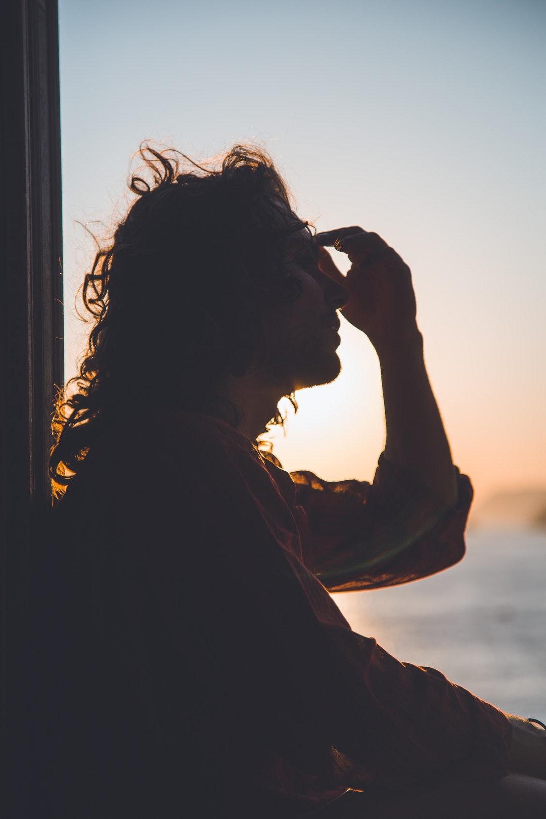 man holding forehead under sunset
