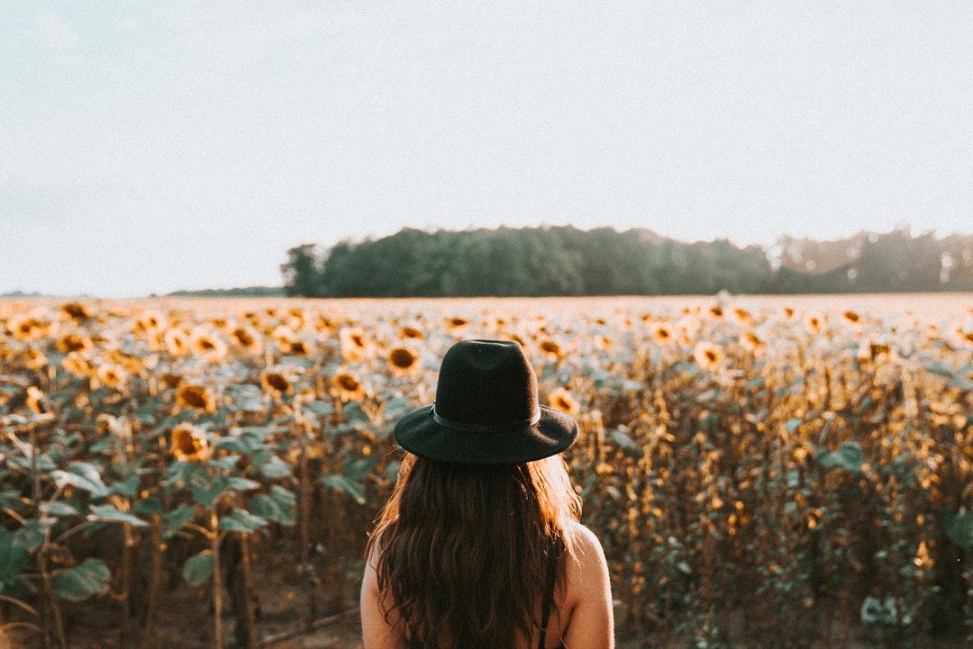 woman standing on sunflower garden