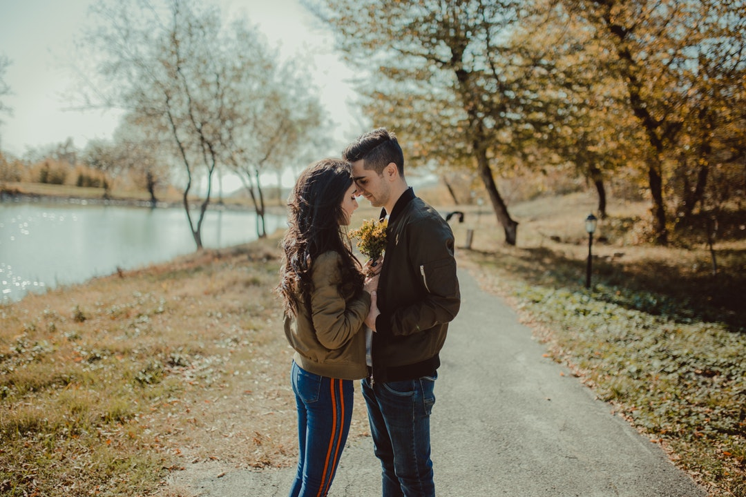 man and woman facing each other standing on footpath beside body of water