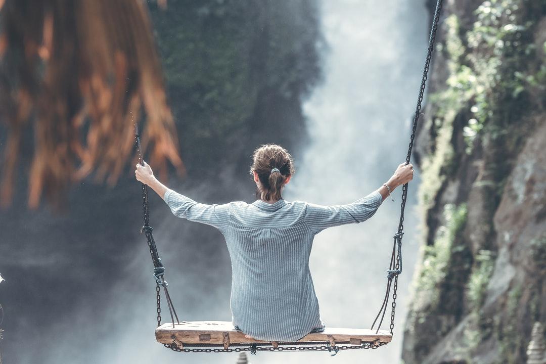 woman sitting on swing near waterfall