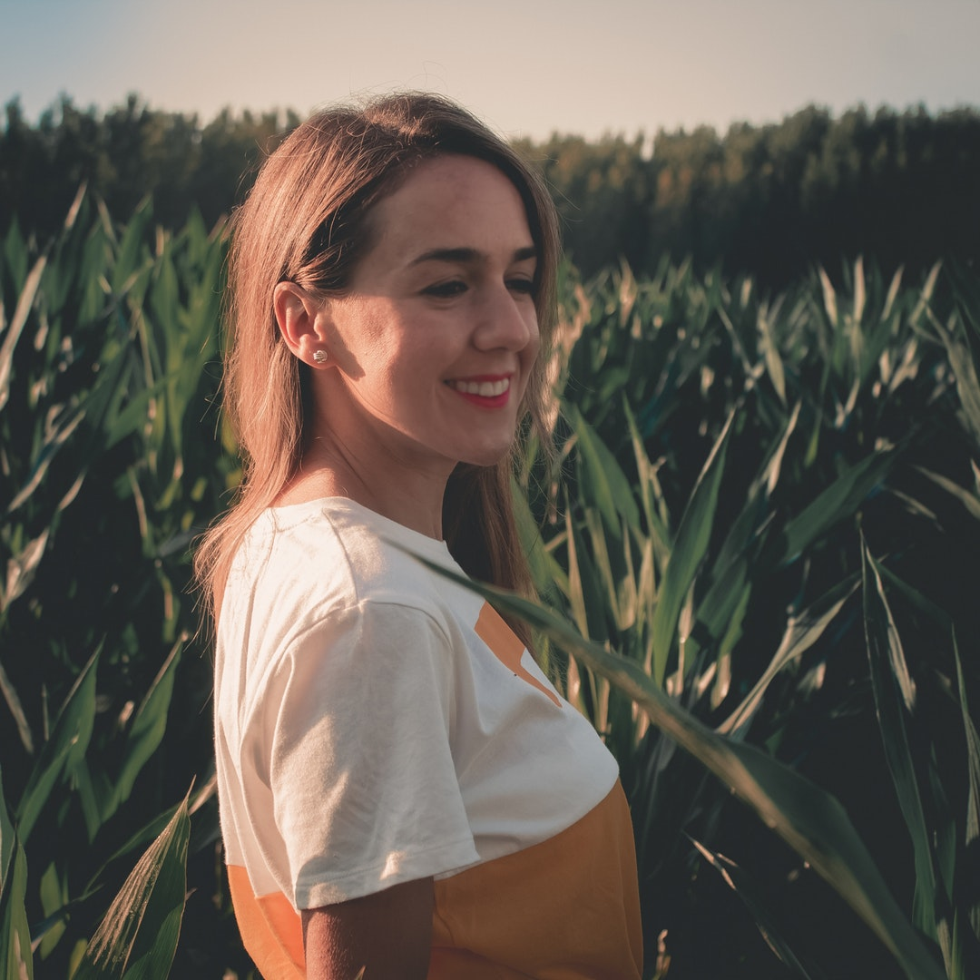 woman smiling beside green leaves during golden hour