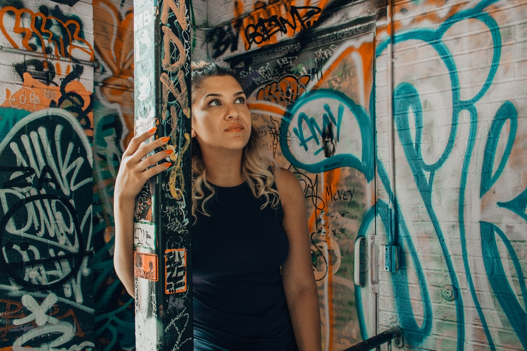 woman wearing black sleeveless shirt holding on post with graffiti using left hand staring on walls with assorted graffiti