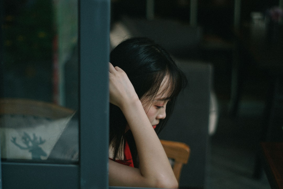 woman sitting down with hand near hair