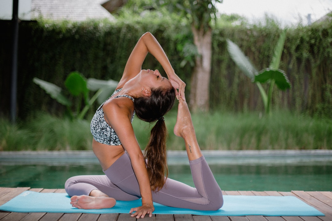woman performing yoga on blue mat during daytime