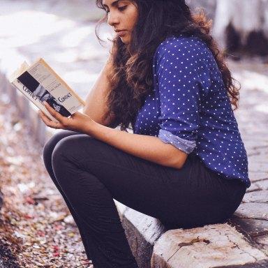 girl reading on the sidewalk