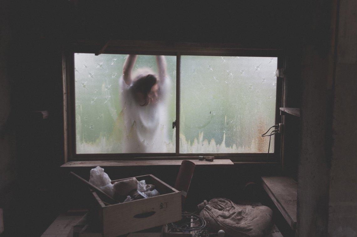 woman standing outside window