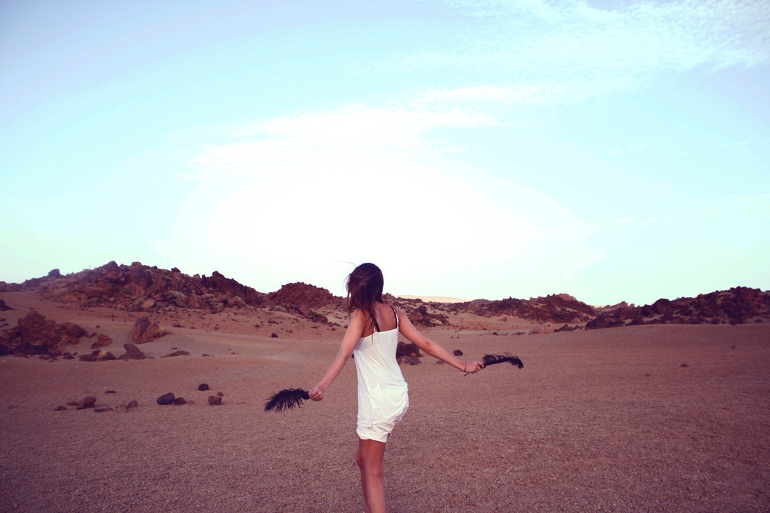 A carefree young woman with a black feather in either hand in the middle of a barren rocky plain