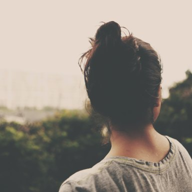 girl with a top knot looking away in the distance