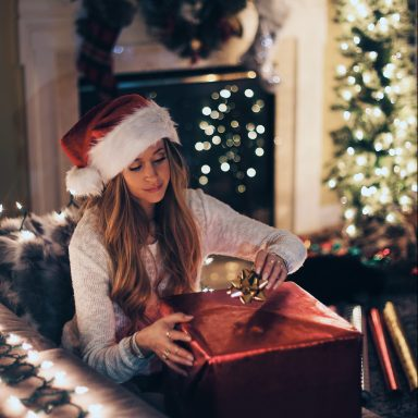 woman wrapping present in santa hat