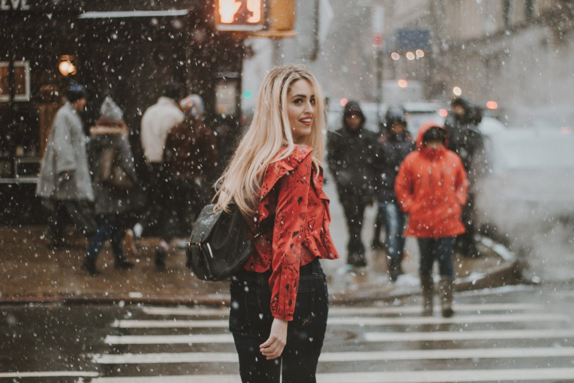 Girl walking through city in snow