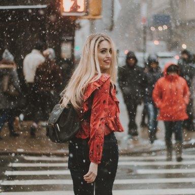 Girl walking through city in snow