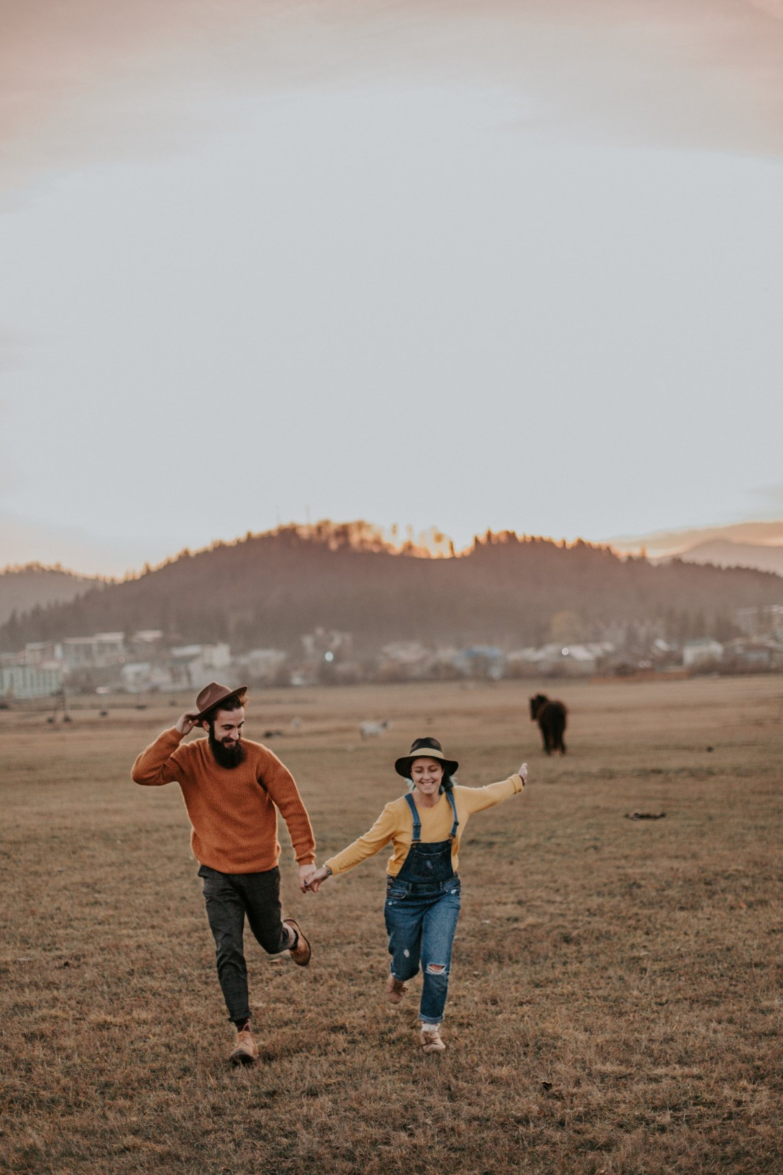 couple running happily through a field