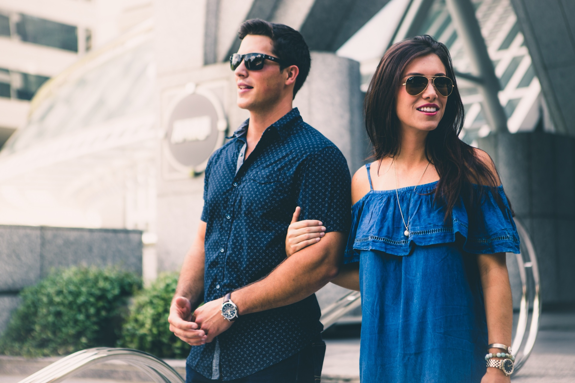 girl and guy walking and leading each other in sunglasses