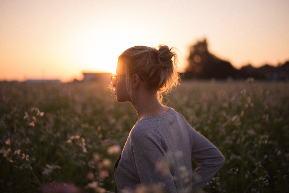 girl in a field with a sunburst