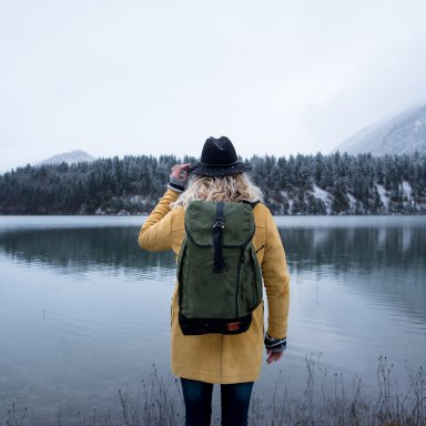 girl backpack lake hat trees