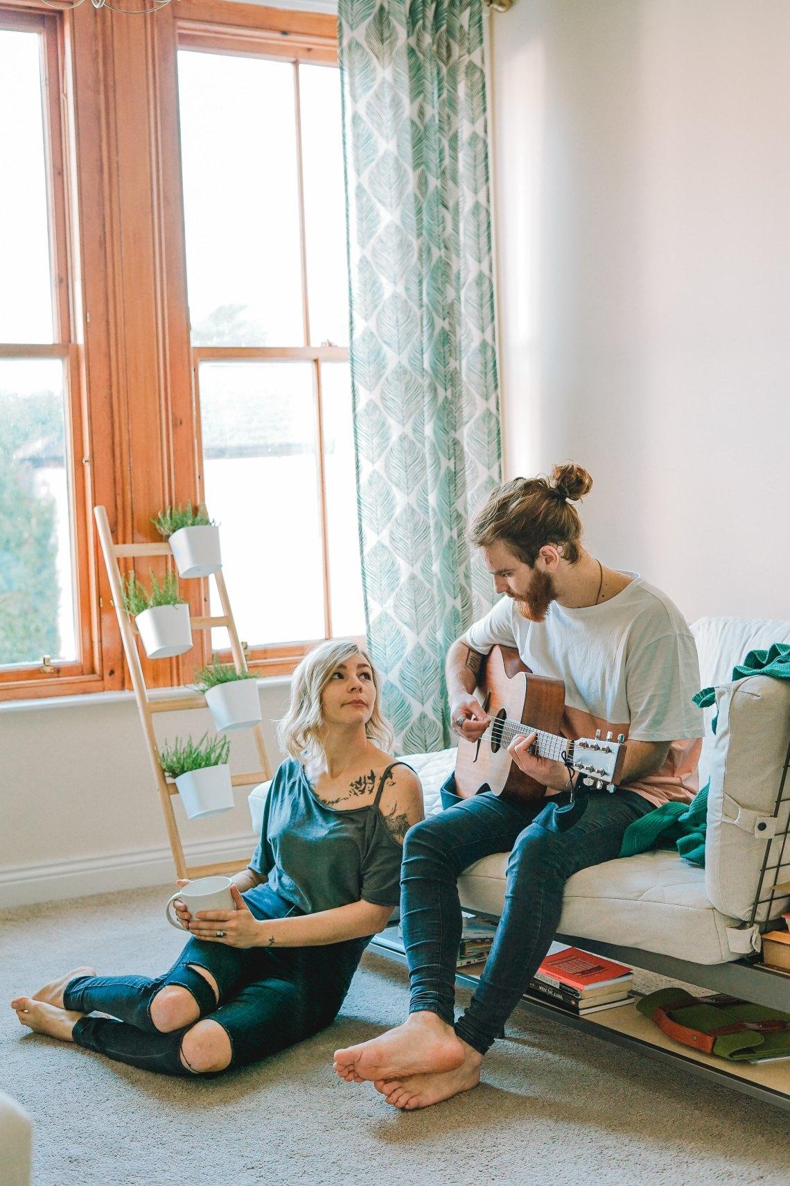 woman watching man play guitar