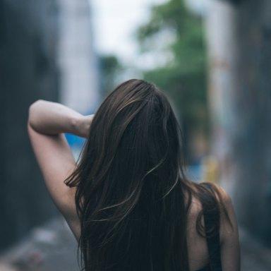 long haired woman running hands through her hair