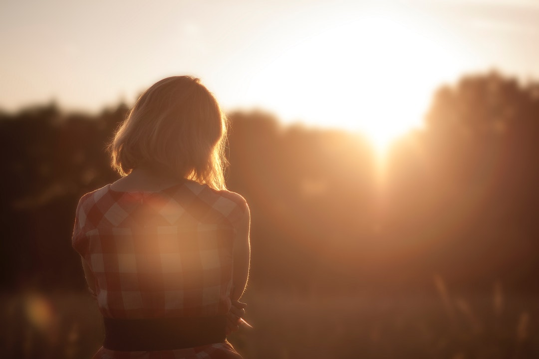 A woman in a checked shirt sits in contemplation as she watches the sunrise through trees.