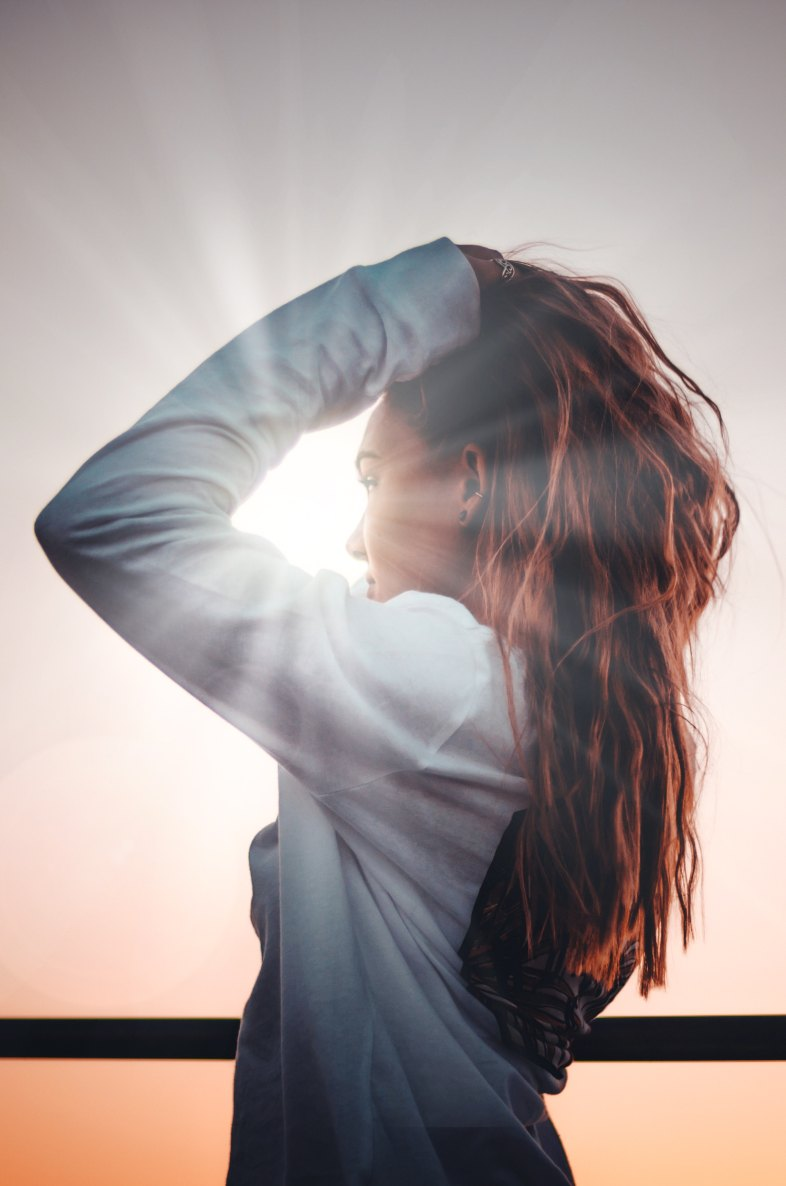 girl standing in front of a sunbeam
