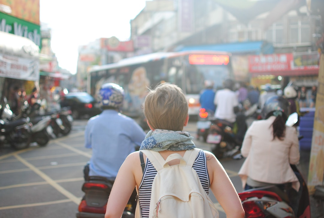 A short-haired woman with a backpack walking through a busy square