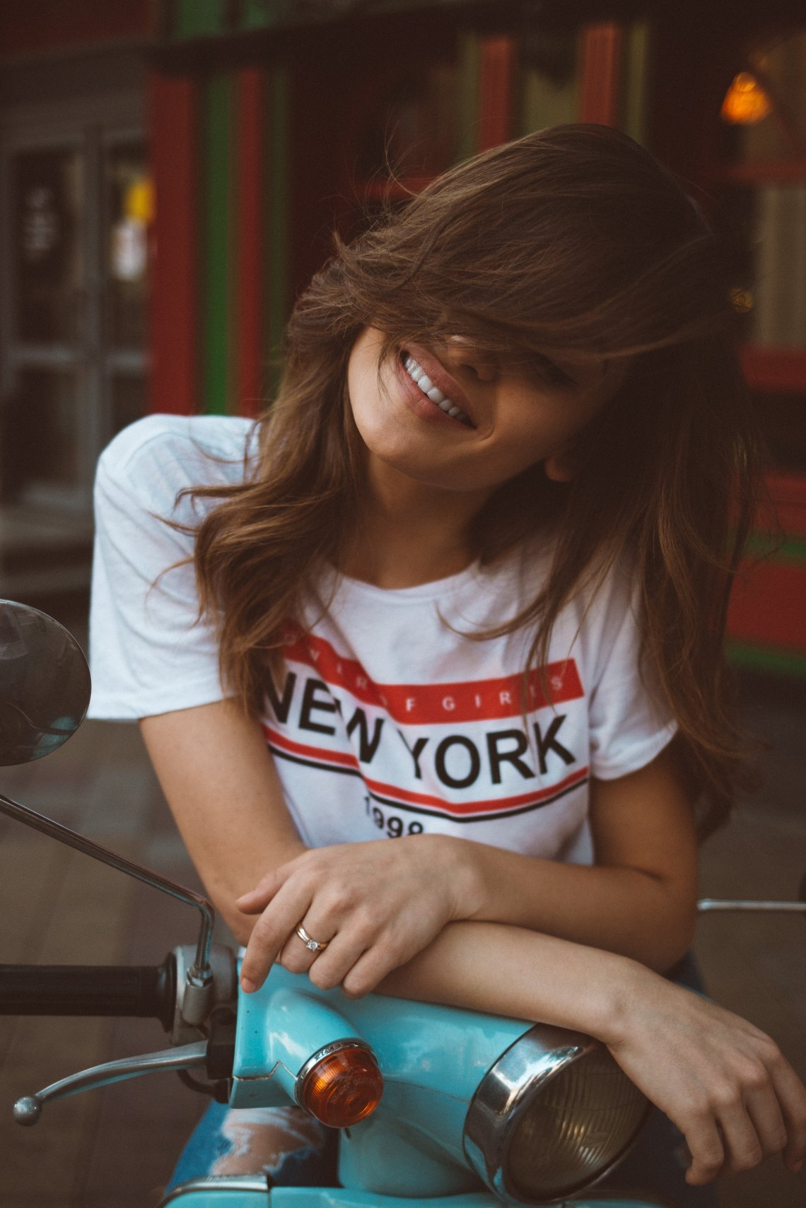 girl laughing in a new york shirt
