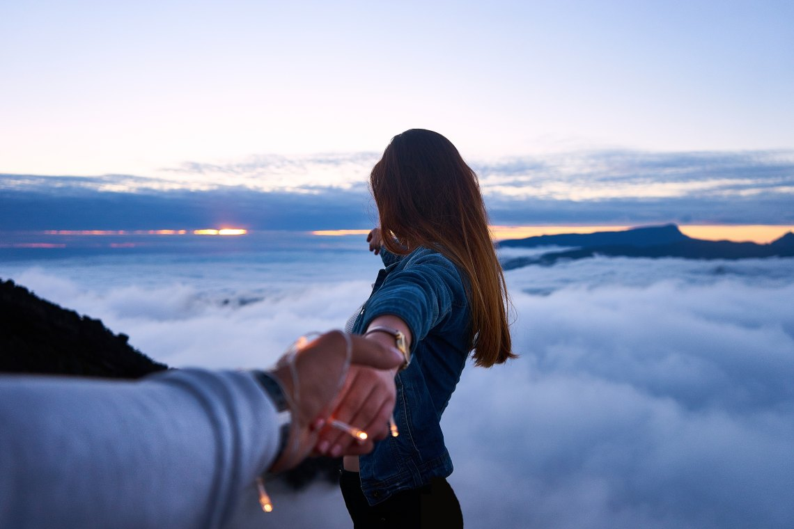 couple holding hands over beautiful clouds