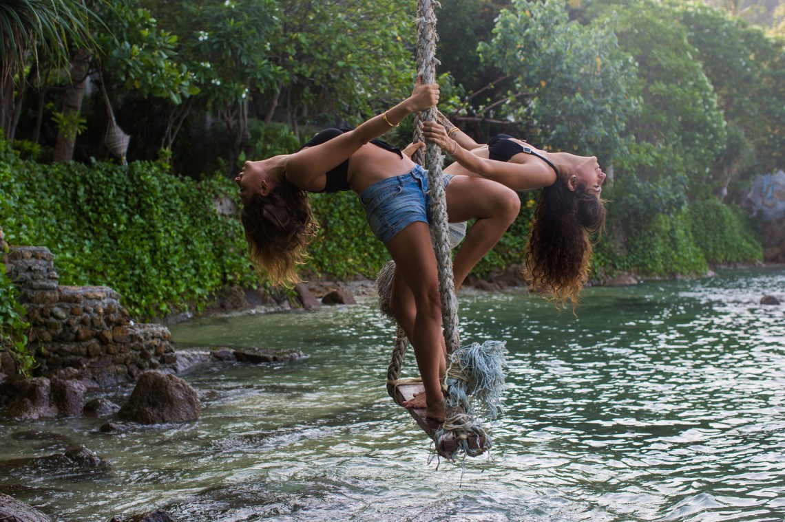 two women swinging on a rope